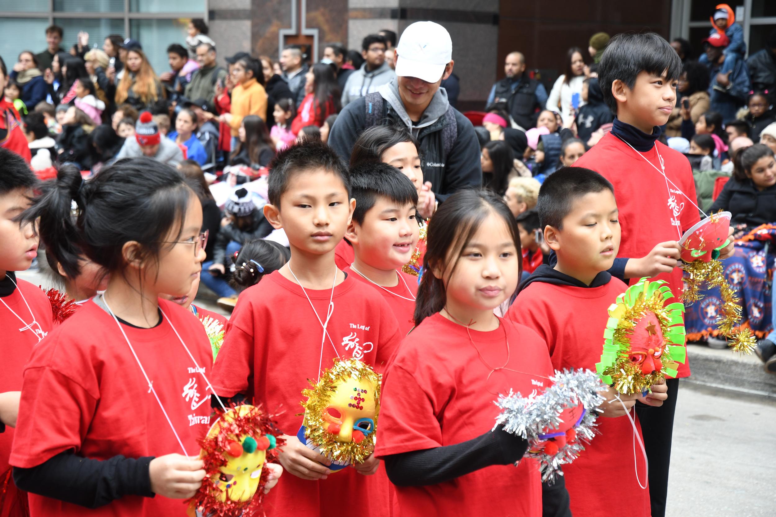 小朋友穿上紅色制服手持小獅子面具,色彩亮麗十分顯眼。