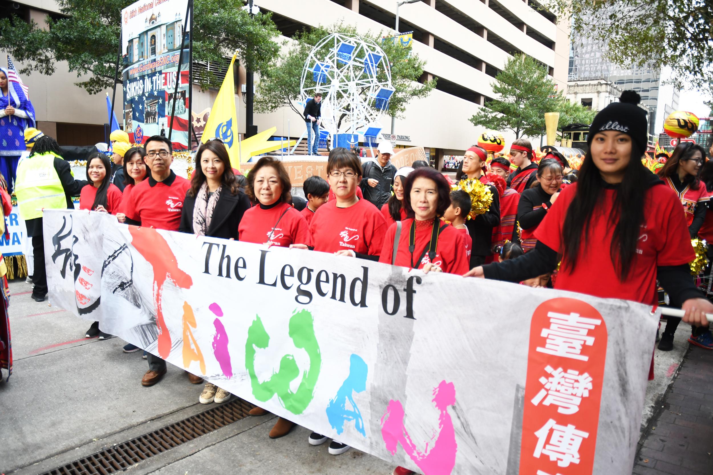 林映佐(右六)、金俊家(右四)、隊員及嘉賓手持台灣傳奇前導旗幟在出發前合影。