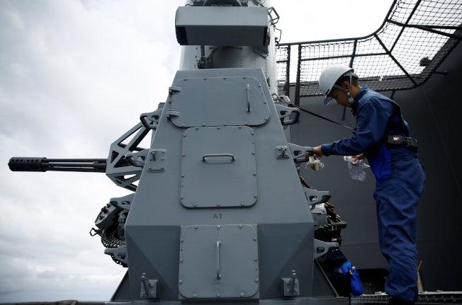一名日本船員在擦拭方陣近迫武器系統。(路透)