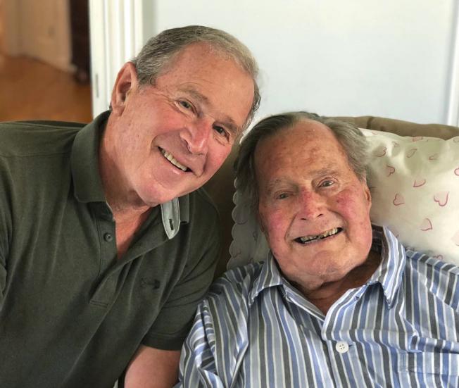 2018年6月,老布什和儿子小布什合影。(美联社)