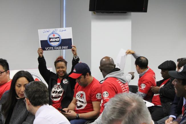 獨立司機工會成員在TLC投票前高舉標語,要求TLC通過新規提高電召車司機最低時薪。(記者張筠/攝影)