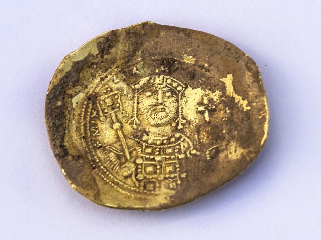 考古學家近日在北以色列的古代地中海港都凱撒利亞,找到一個據信藏在牆內900多年的青銅罐,發現裡面藏有24枚金幣及1只金耳環,推測物主可能遇上西元1101年的十字軍攻城,企圖將財富藏起,等風頭過後再找回來。(Getty Images)