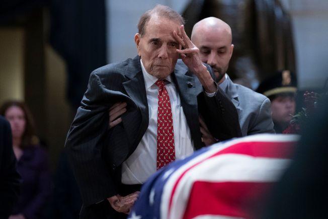 前國會參議員杜爾在侍從扶持下,艱難從輪椅上站了起來,向老布希總統行禮致敬。(Getty Images)