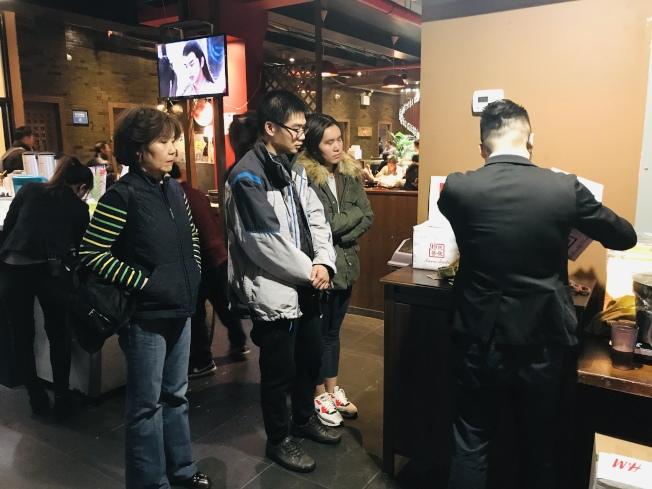 湖北同鄉會會長張輝(左一起)、龔先生、趙亞云看著99餐廳工作人員拆開捐款箱。(記者黃伊奕/攝影)