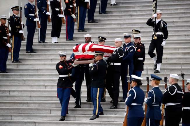 覆蓋國旗的老布希靈柩緩緩被抬下國會山莊台階。(Getty Images)