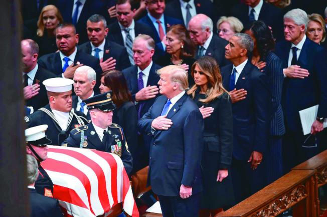 美國5日為老布希總統舉行國葬,圖為川普總統夫婦(右六右五)、前總統歐巴馬夫婦(右四右三)及柯林頓夫婦(右二右一)撫胸向老布希總統靈柩行禮。(Getty Images)