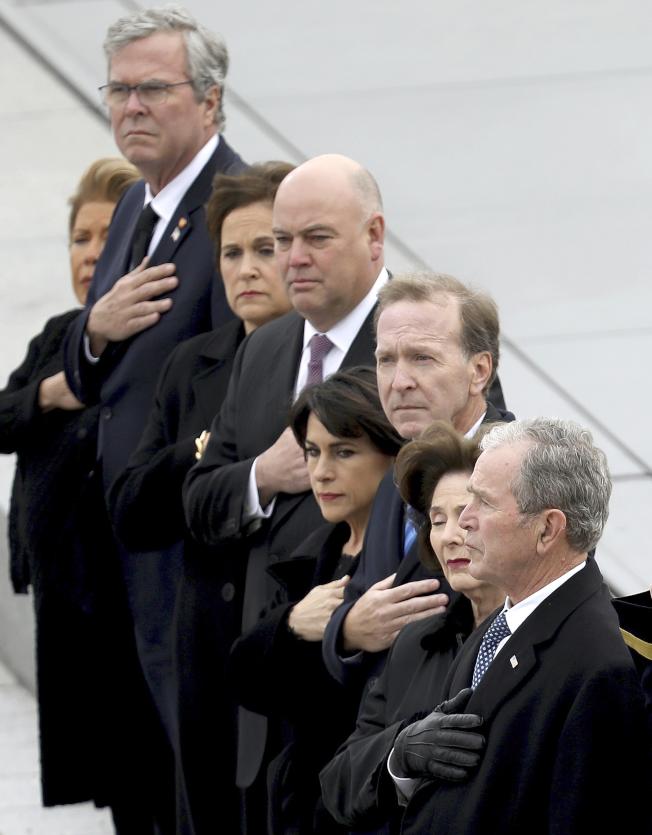 小布希總統(右一)為首的家屬向老布希的靈柩致敬。(美聯社)