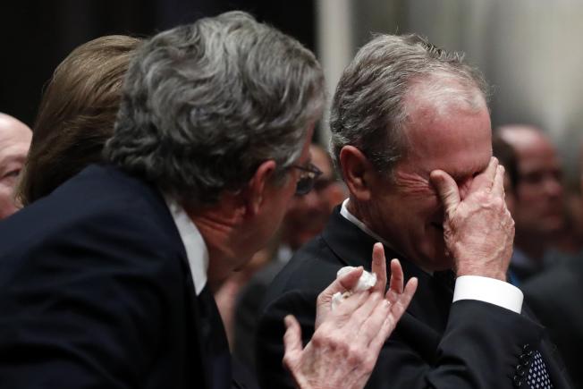 老布希喪禮上,小布希低頭拭淚,弟弟傑布布希則為父親鼓掌。(Getty Images)