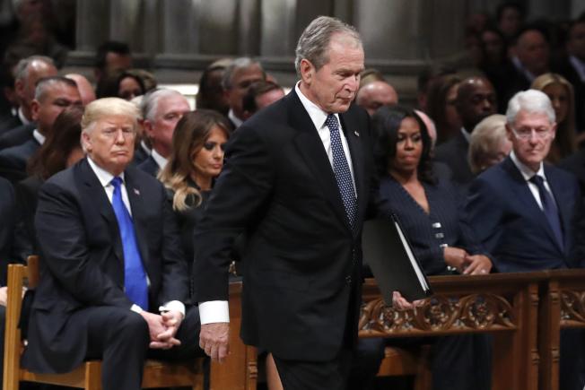小布希總統起立準備走上講台致悼詞,後左為川普總統夫婦,後右為米雪兒歐巴馬及柯林頓總統。(美聯社)