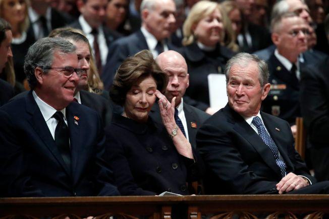 蘿拉布希(中)在老布希喪禮上拭淚,小布希(前右)及傑布布希在旁笑著注視。(Getty Images)