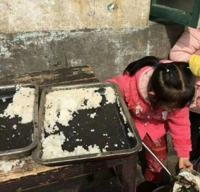 多張網傳現場照片顯示,蒸熟的大米上爬著不少蒼蠅,一位紅衣小女孩正在旁邊打飯。(視頻截圖)