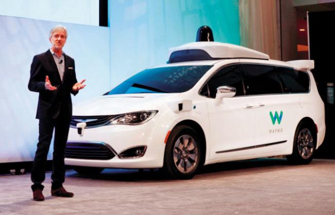 從Google獨立出來的自駕車公司Waymo 5日宣布,推出全美首創的商業自駕車叫車服務。圖為Waymo的自駕車和執行長克拉夫錫。(Getty Images)