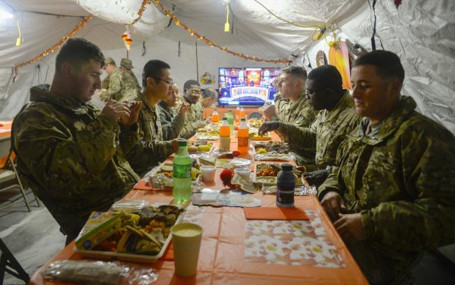 一名美軍數周前接到部署美墨邊界的命令,心裡有點不安,因為這名生在中國的軍人,本身就是非法移民。圖為邊界的美軍日前在帳篷裡享用感恩節「大餐」。(美聯社)
