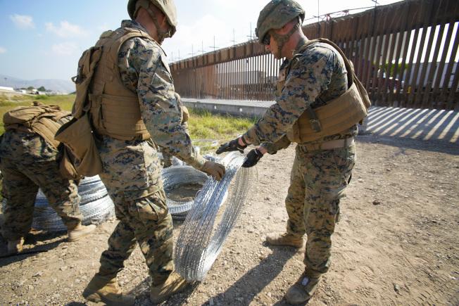 一名喪失合法居留身分的華裔美軍數周前接到部署命令,隨部隊派往美墨邊界支援邊境巡邏員,逮捕任何非法入境的人。圖為布署在邊界的美軍準備在邊境牆上加裝鐵絲網。(TNS)