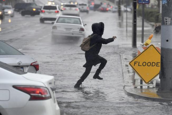 強烈氣團在南加州降下超過2吋雨量,陣風風速達到將近70哩。雨雪交加導致交通大亂。圖為加州居民設法跳過淹水街道。(美聯社)