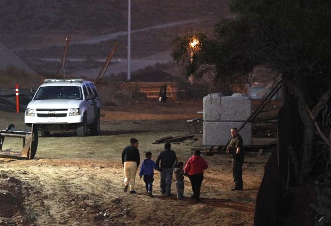 移民大篷車隊的一名19歲宏都拉斯婦女,與家人翻越美墨邊界圍牆後,於24小時內分娩產子,成為大篷車隊非法移民生下「定錨嬰兒」首例。圖為在加州攀爬邊界牆的中美洲移民,帶著孩子走向等候逮捕他們的邊境巡邏員。(美聯社)