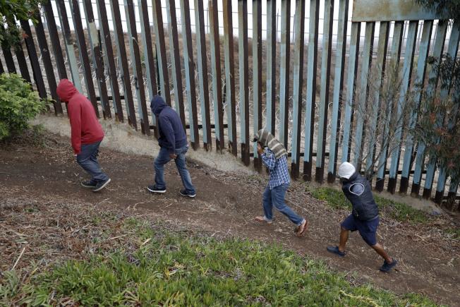 美墨邊境築牆預算談不攏,聯邦政府仍然面臨關閉壓力。圖為中南美洲移民在提璜納圍牆邊尋找機會溜進美國。(美聯社)