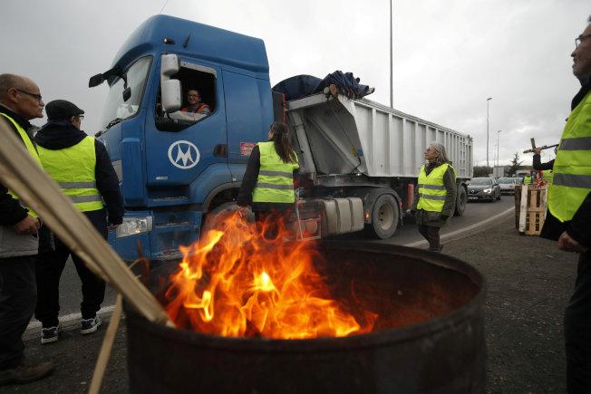 穿著黃背心的抗議者占領法國一處公路匝道。(路透)