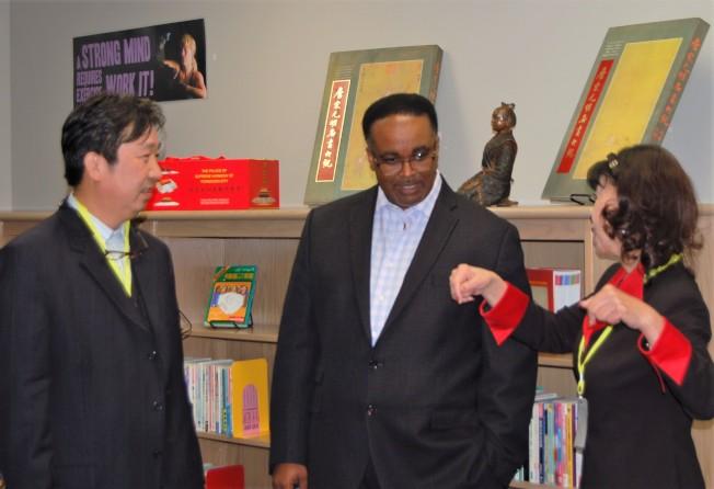 在斯塔福德市立學區高中圖書館中文圖書部的成立儀式上,譚秋晴(右)與斯塔福市立學區負責人羅伯特-博斯蒂克(中)、休士頓古董拍賣公司董事長吳因潮交談。(記者賈忠/攝影)