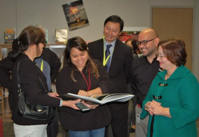 斯塔福市立學區高中部的學生在欣賞王維力老師捐贈的畫冊。(記者賈忠/攝影)