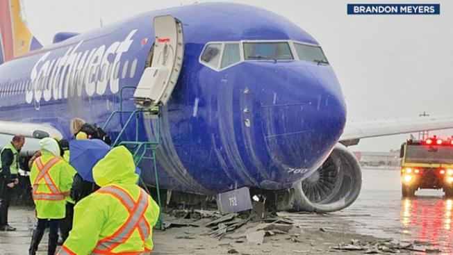 圖中可見西南航空的波音737客機,在滑出跑道後,終於停了下來,但航機已經「跪下」,著陸使用的著陸架和輪胎都已毀壞,不見了,整個客機則平躺在地上。(取自推特)
