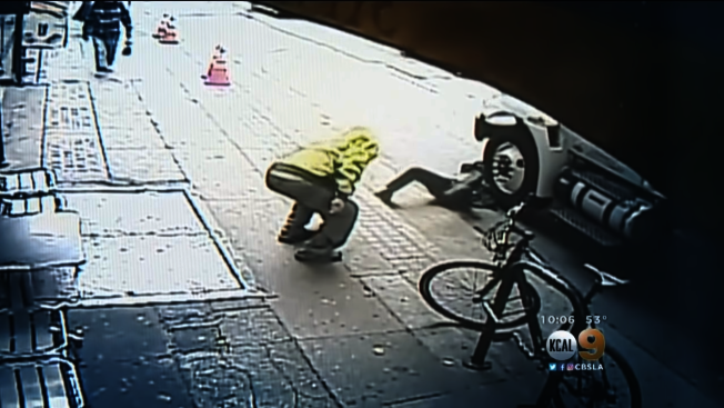 黃衣男將西裝男推倒後,若無其事的撿起物品離去。取材自YouTube