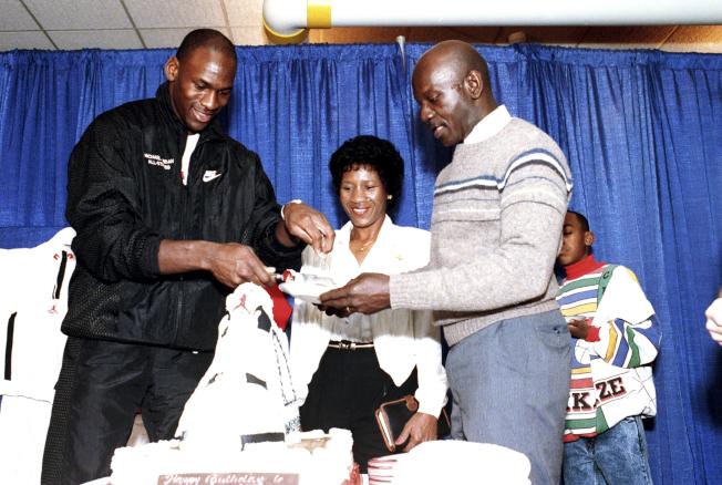 1989年飛人喬丹(左)慶祝26歲生日,在母親(中)注視下,他切了塊蛋糕給父親詹姆斯。詹姆斯1993年7月23日遇劫喪命,被判終身監禁的凶手現在要翻案。(美聯社)