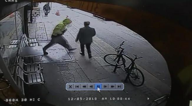 鎖定目標後,等候在店家門口的流浪漢突然對路人發起攻擊。(警方提供)