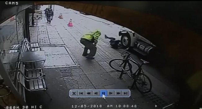 受害人撞上側面駛來的卡車前輪。流浪漢趁機撿起地上的錢包,揚長而去。(警方提供)
