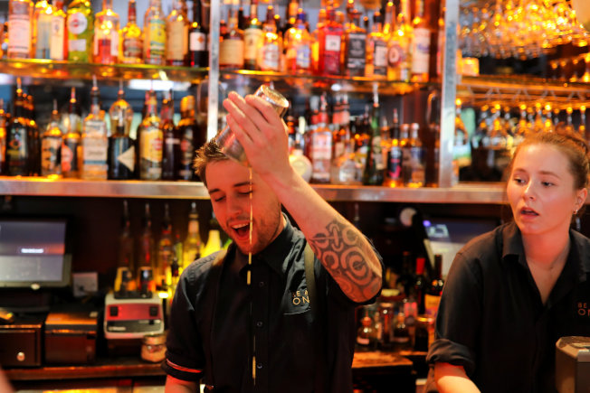 比起在咖啡廳和地鐵等地,酒吧的消費者在酒精的催化下更願意與他人談話,圖中調酒師在調製雞尾酒。(路透)