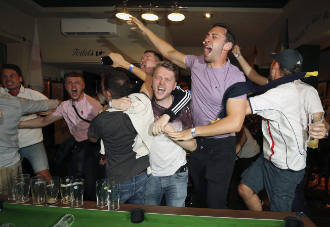 英國足球迷在酒吧裡看世界杯,一邊喝啤酒歡呼。(美聯社)