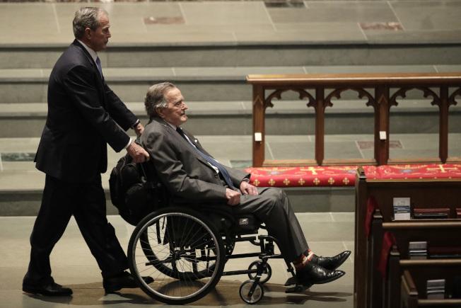 人瑞與他們的老孩子,是漸趨老化的家庭結構新現象。圖為72歲的小布希總統今年4月推著高齡94歲、乘坐輪椅的父親老布希總統,出席老布希夫人芭芭拉的喪禮。(美聯社)