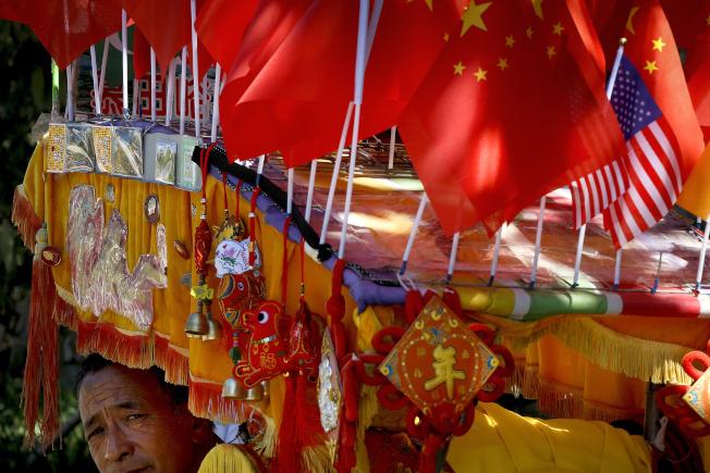 中國宣布多項措施,緩解美中貿易衝突,圖為北京攤販展售的中美國旗及過年飾品。(美聯社)