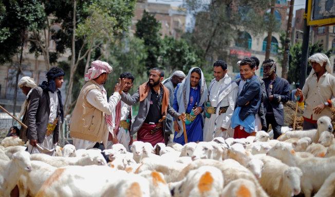 一群人在葉門首都沙那的牲畜市場購買祭祀用動物,但市場外往往有一群乞丐餓著肚子。(路透)