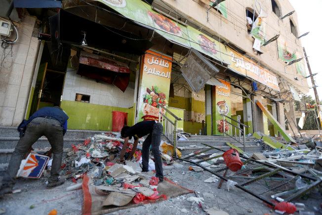 葉門餐廳遭攻擊,員工在清理瓦礫碎片。(路透)