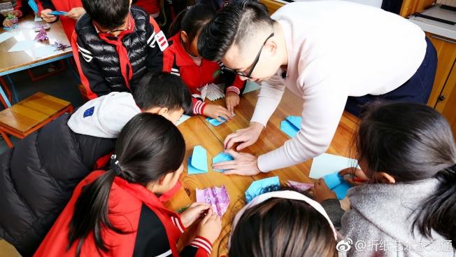 劉通教小朋友摺紙。(取材自微博)