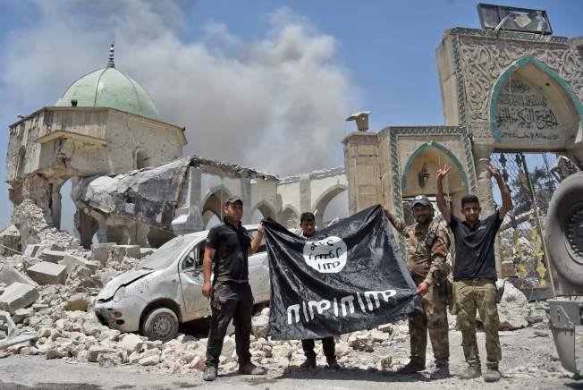 伊拉克反恐部隊攻下伊斯蘭國據點摩蘇爾後,展開擄獲的伊斯蘭旗幟。(Getty Images)
