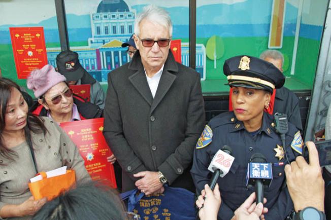 賈斯康(中)和警局灣景分局長馬修斯(右)在肖化區宣傳防範金光黨。(記者李晗/攝影)