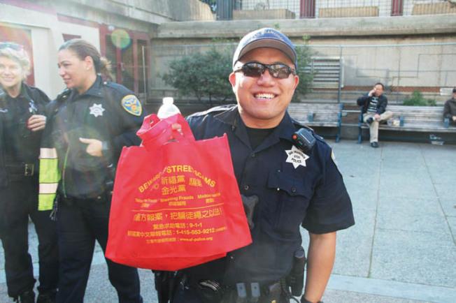 華埠警員馬健明參與社區外展,拿著防範金光黨騙案的宣傳袋子。(記者李晗/攝影)