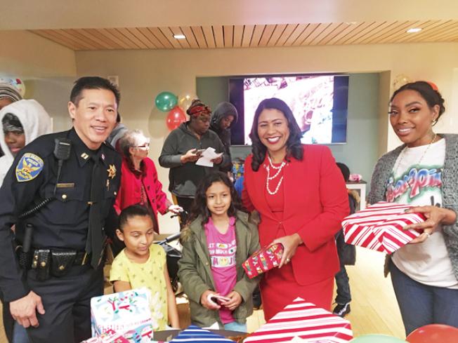 市長和Robert Yick警官一起參加華埠社區發展中心的假日玩具贈送活動。
