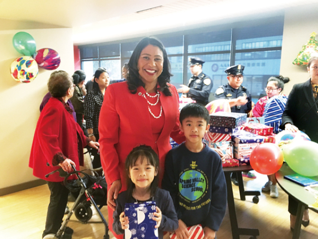 市長參加在華埠社區發展中心舉辦的假日玩具贈送活動,與小朋友在一起。