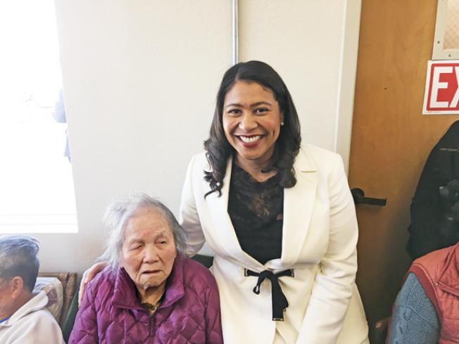 在最近舉行的可負擔屋開放、紀念前市長李孟賢的活動中,布里德市長與一位99歲的長者居民合影。