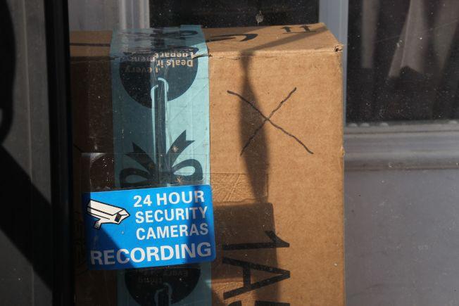 耶誕假期是貨品遭竊的高峰期,一名消費者在門外豎立「24小時保安攝影」來阻嚇「門廊大盜」。(Getty Images)