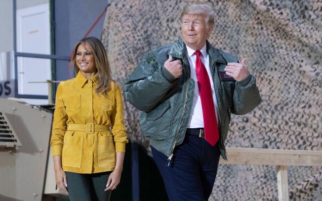 川普總統(右)26日突然偕同妻子(左)到伊拉克勞軍,履行他前往美軍所在的一個戰區視察的承諾。Getty Images
