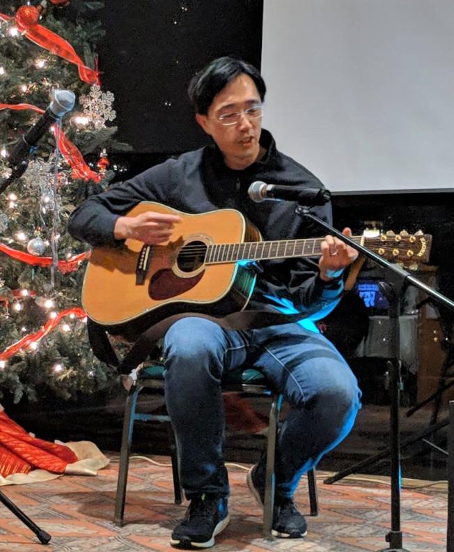經文處之徐佑典在同樂晚會中吉他彈唱「海裡來的沙」。(勒星頓中文學校提供)