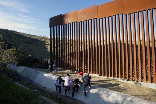 宏都拉斯移民從墨西哥提璜納準備翻越美墨邊境的鐵欄杆邊牆。(Getty Images)
