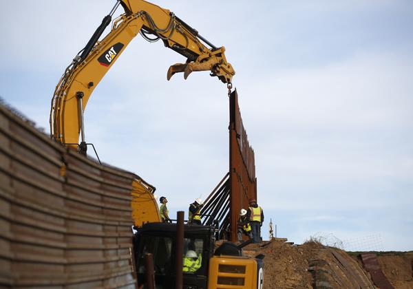川普總統把興建邊牆的爭議直接訴諸民意,圖為施工人員在與墨西哥提璜納交界處整修美墨邊牆。(美聯社)