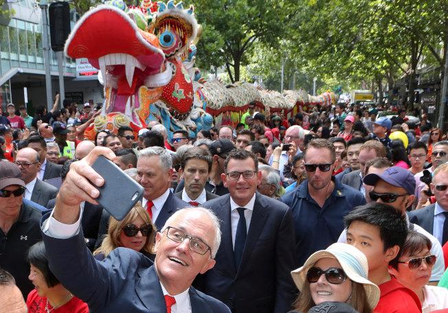 澳洲2019年將舉行聯邦選舉,移民逐漸成為爭議的政治話題。圖為澳洲總理滕博爾2018年參加亞裔農曆年遊行時,開心與民眾自拍。(路透)