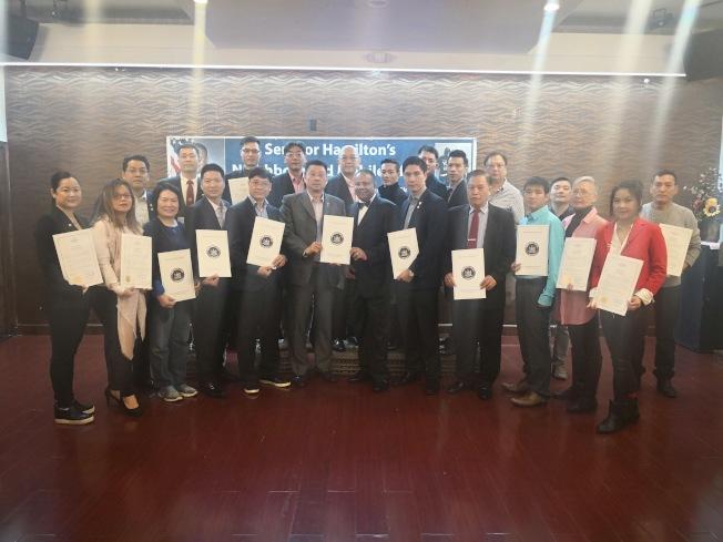 韓文頓(前排左七)為華裔民眾頒發榮譽證書。(記者黃伊奕/攝影)