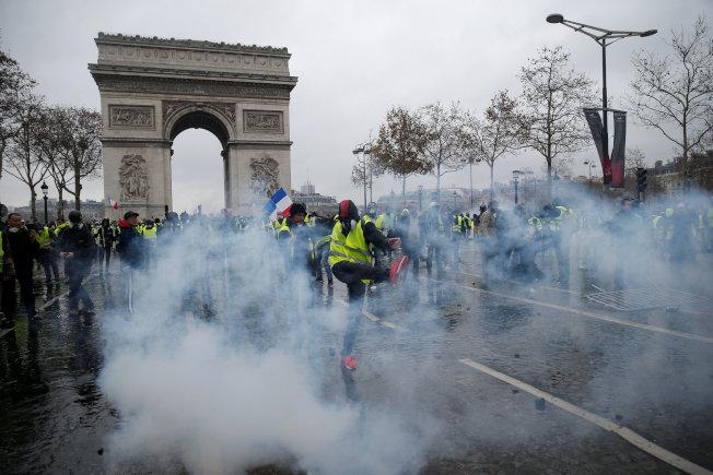 法國黃背心抗議爆發警民衝突,警方發動催淚瓦斯驅離群眾。(路透)